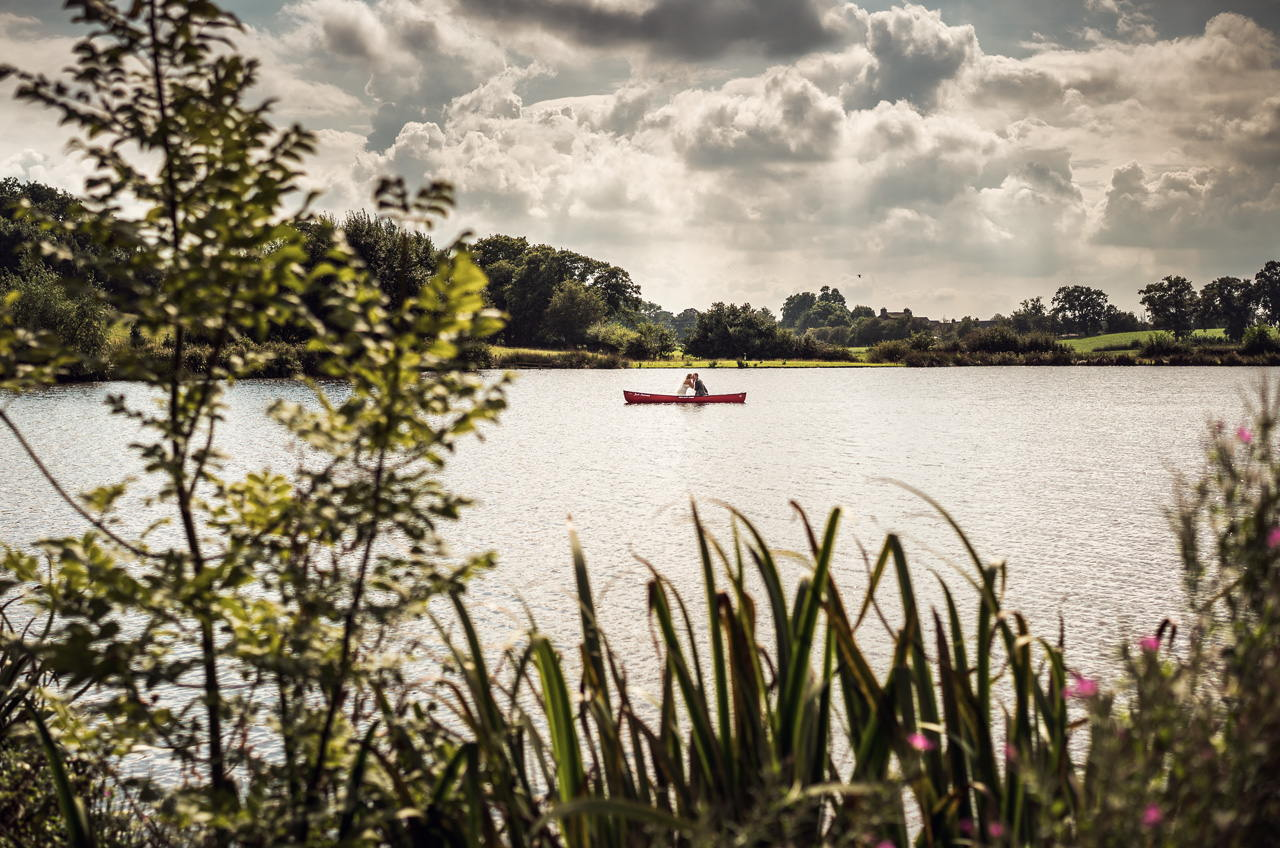 wedding photo couple in canoe on the lake at Sandhole Oak Barn