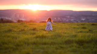 A girl plays in a field at sunset at a Pennine Tipi wedding