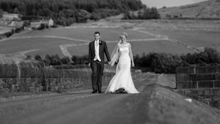 Saddleworth farm barn wedding, walking along the reservoir path - the bride in a stunning fishtail dress.