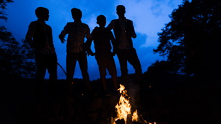 Four boys by a campfire late on at a Llyn Gwynant wedding.